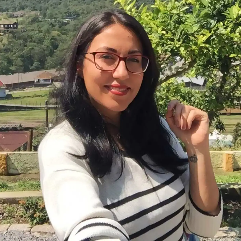 Anna Grazielly Marques, da Dr. JONES, veste blusa branca com listras pretas e sorri para a câmera. Ela tem pele clara, cabelos compridos escuros e lisos, tatuagem no punho esquerdo e usa óculos de armação vinho.