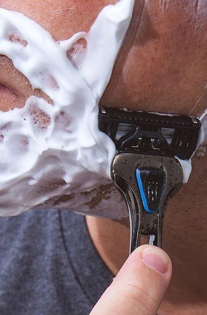 Em artigo sobre irritação na pele após fazer a barba, imagem mostra homem de pele clara utilizando espuma no rosto e o barbeador The Razor, da Dr. Jones, para barbear-se.