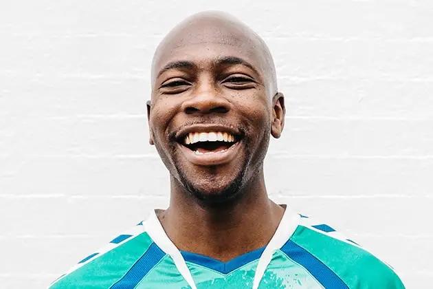 Homem negro, careca, com cabeça raspada por lâmina, sorri para a câmera, usando, em frente a fundo branco neutro, uma camisa ciano com listras azuis, estampada.
