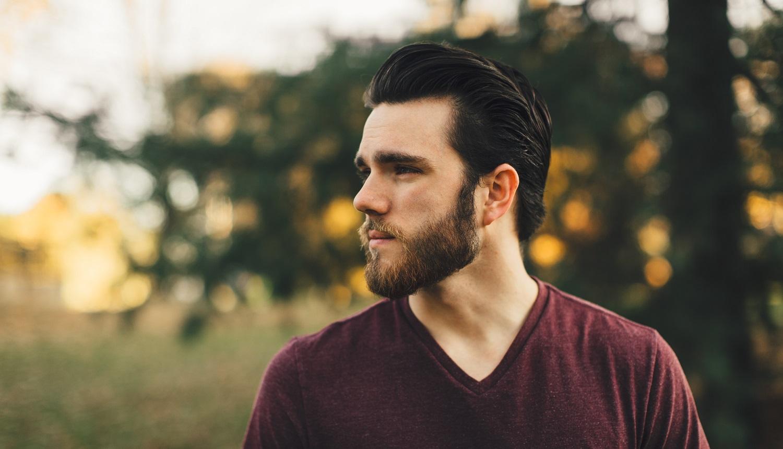 Homem de pele clara, com barba, cabelo escuro para trás estruturado com pomada de cabelo, camisa vinho, em frente a uma árvore com sol ao fundo.