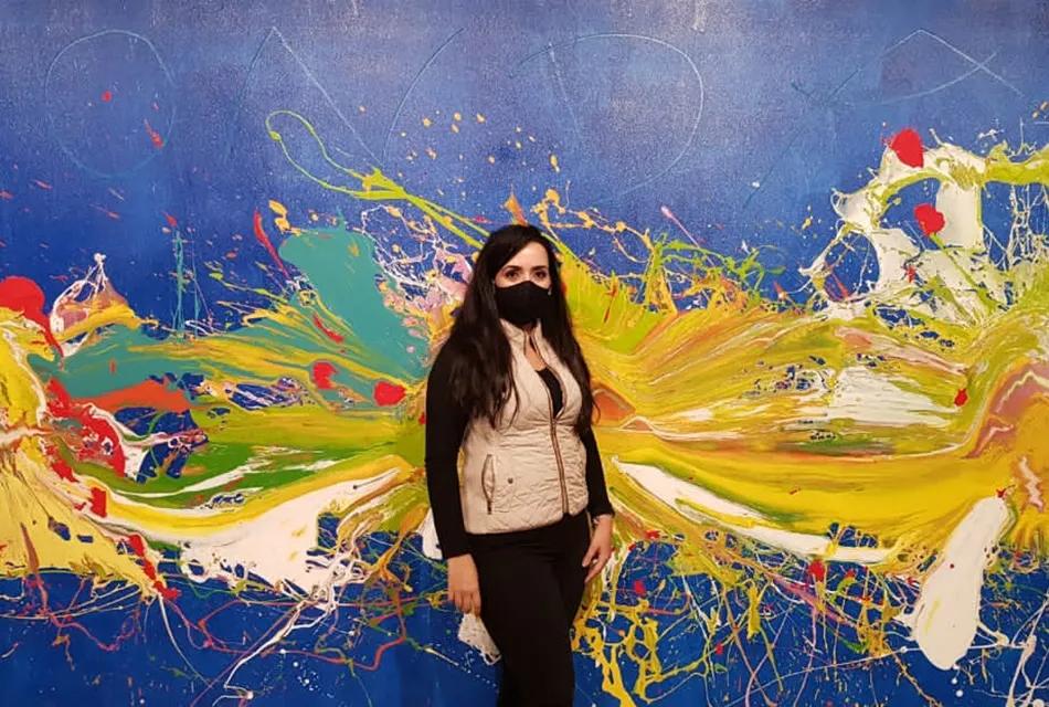Foto de Natália de Lucca, analista de produtos da Dr. JONES, usando colete bege, blusa preta e calça preta, de máscara para prevenção à COVID-19, em frente a obra de arte: um quadro azul com motivos multicoloridos.