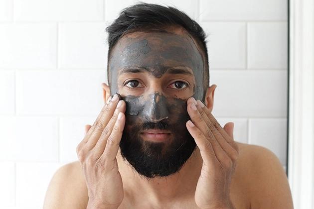 Em artigo sobre o poder detox do carvão, imagem traz homem de pele clara, cabelo curto e liso, raspado nas laterais, e barba escura passando creme de cor cinza no rosto.