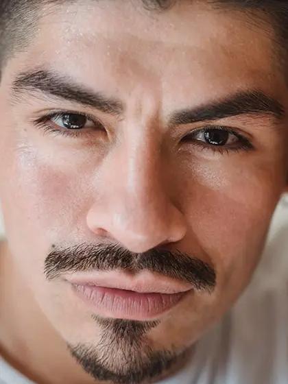 """Foto em que se destaca o rosto de homem de pele clara com """"barba âncora"""", isto é, cavanhaque e bigode desconectado do restante, olhando direto para a câmera e usando camiseta branca."""
