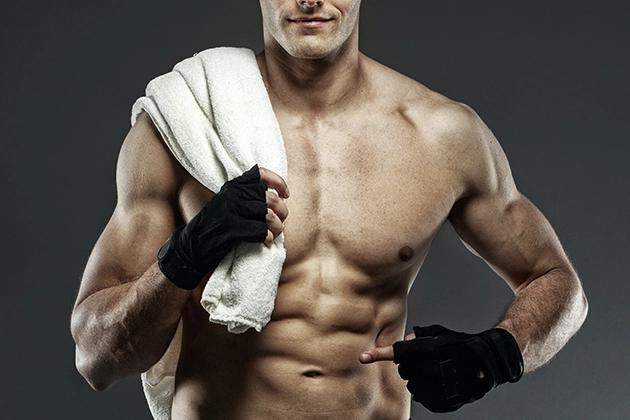 Em artigo sobre 6 séries de exercícios para fazer em casa, imagem traz torso de homem branco sem camisa, toalha branca no ombro direito, luvas pretas para exercício, apontando para o abdômen.