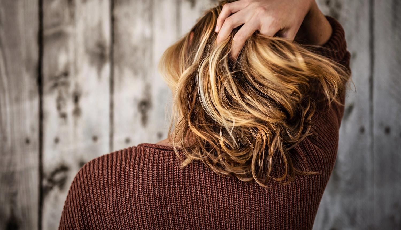 Imagem traz um homem de cabelos loiros, de costas, passando a mão nos cabelos sem caspa. Ele está de frente a uma cerca de madeira e usa blusa marrom. A foto alude a uma vida sem caspa com o uso do climbazol.