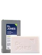 Embalagem e barra do sabonete Hydra Soap, da Dr. JONES. A barra é branca, e a embalagem é cinza.