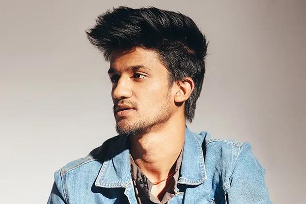 Foto de homem jovem, pele parda, cabelos escuros com topete, camisa marrom e jaqueta jeans, com barba por fazer, olhando para a direita, em frente a fundo neutro acinzentado.