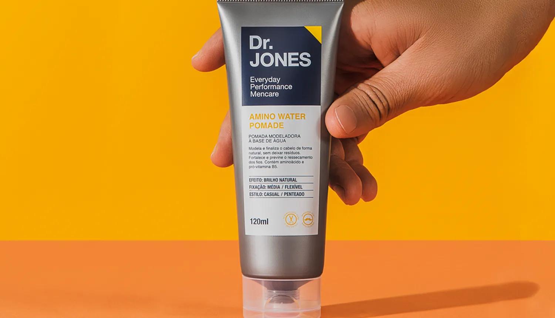 Em fundo amarelo com mesa laranja, foto da Amino Water Pomade, pomada de cabelo da Dr. JONES, para cabelos masculinos, que utiliza Carbocisteína na fórmula. A embalagem cinza é segurada por uma mão.