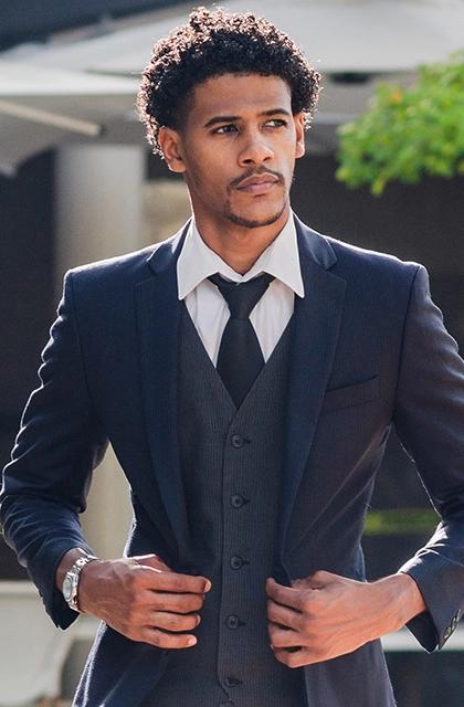 Foto de homem pardo, de cabelos cacheados, cavanhaque desenhado, usando terno cinza-azulado e colete cinza. A camisa é branca e a gravata, cinza.