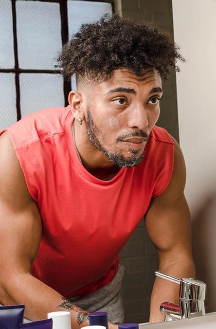 Em artigo sobre falhas na barba, imagem mostra homem negro, com camiseta sem mangas laranja, cabelo cacheado e raspado nas laterais, barba aparada, tendo aplicado creme no rosto.