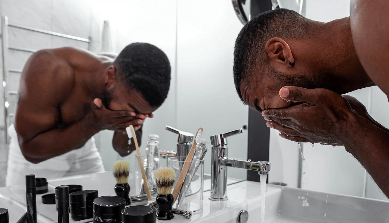 Homem negro sem camisa está na pia lavando o rosto em frente ao espelho. Ele aparenta cansado de lavar o rosto várias vezes ao dia, por conta da pele oleosa. Quando ele vai conseguir acabar com essa oleosidade toda?