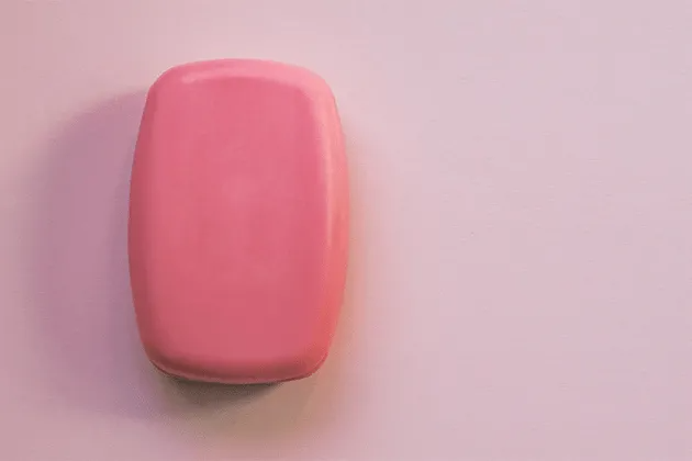 Imagem mostra uma barra de sabonete cor-de-rosa em fundo rosa claro.