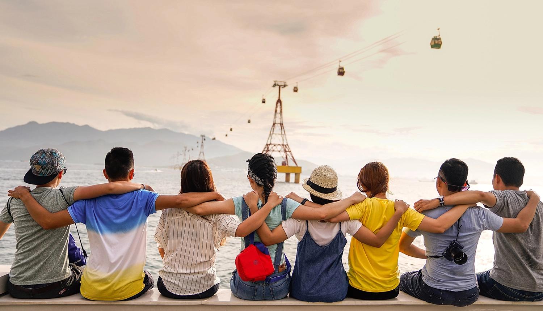Em artigo sobre HIV e aids, a imagem mostra oitos jovens, homens e mulheres, abraçados e sentados em fileira sobre uma mureta, de costas para a câmera, observando o mar. Ao fundo, um teleférico com cabines.