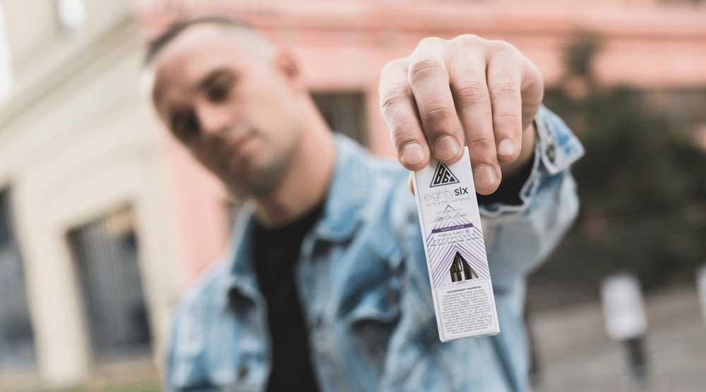 Man holding Eighty Six Purple Punch cartridge