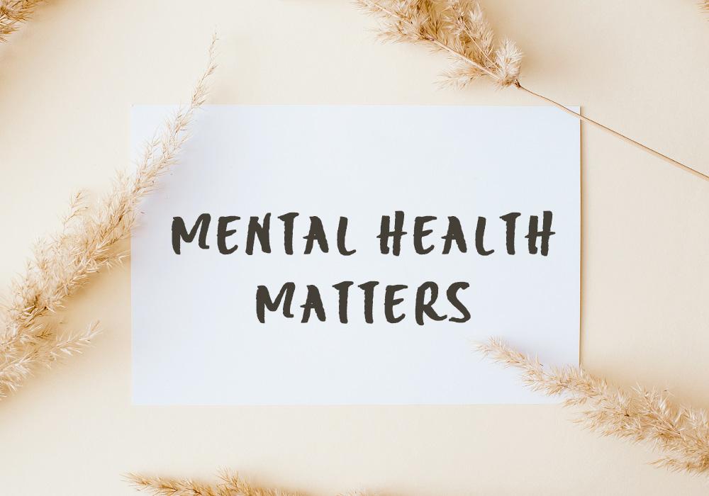 """Die Worte """"Mental Health Matters"""" stehen auf einem weißen Papier, welches auf beigem Untergrund liegt"""