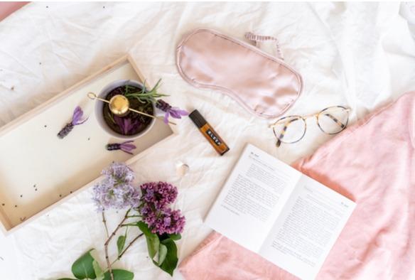 Rosa Schlafmaske und Flieder auf weißem Bettlaken