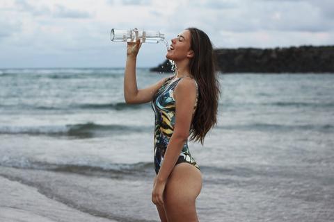 Frau im Badeanzug trinkt aus einer Glasfalsche und steht am Strand