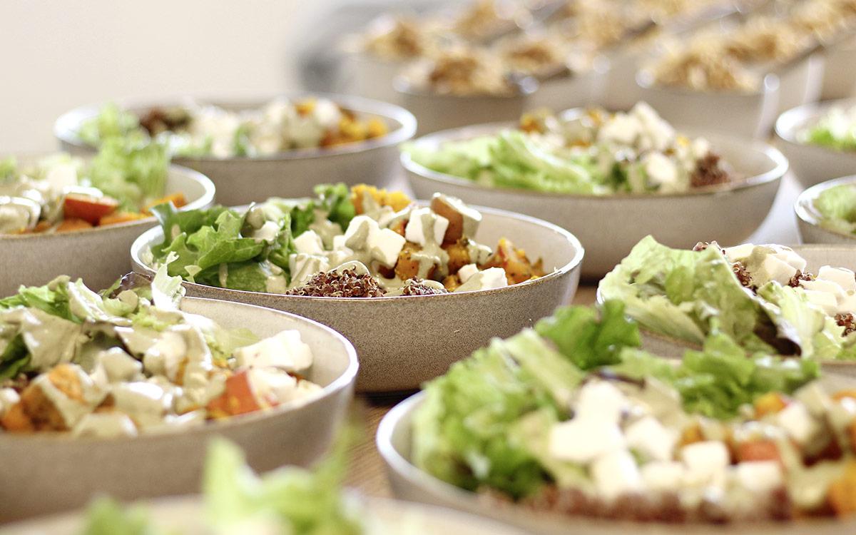 Mehrere Porzellanschüsseln gefüllt mit Ofengemüse, veganen Feta und Quinoa