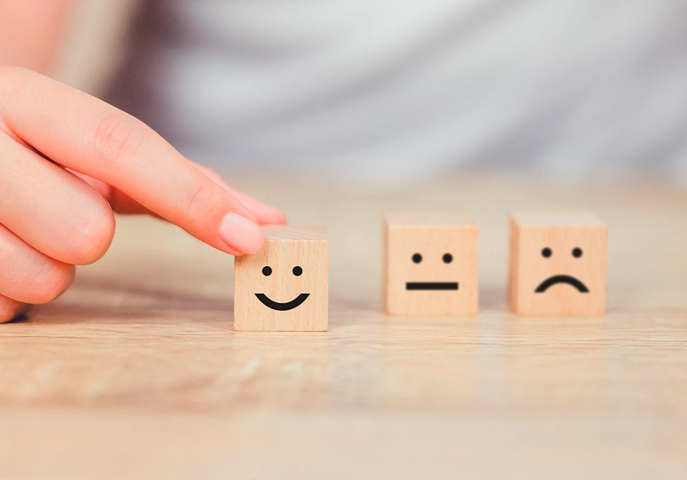 Drei kleine Holzwürfel, die je einen anderen Gesichtsausdruck zeigen und damit die unterschiedlichen Stimmungslagen simulieren sollen.