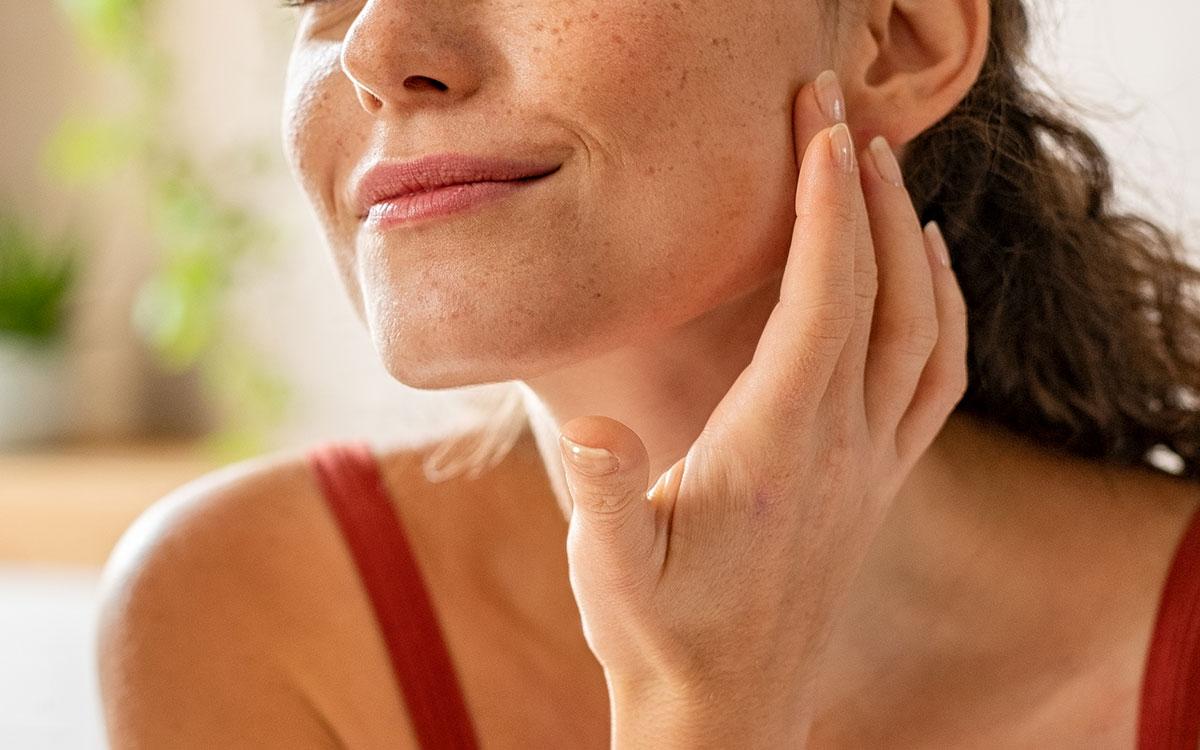 Frau die mit ihren Händen Hautpflege auf den unteren Teil ihrer Wange aufträgt.