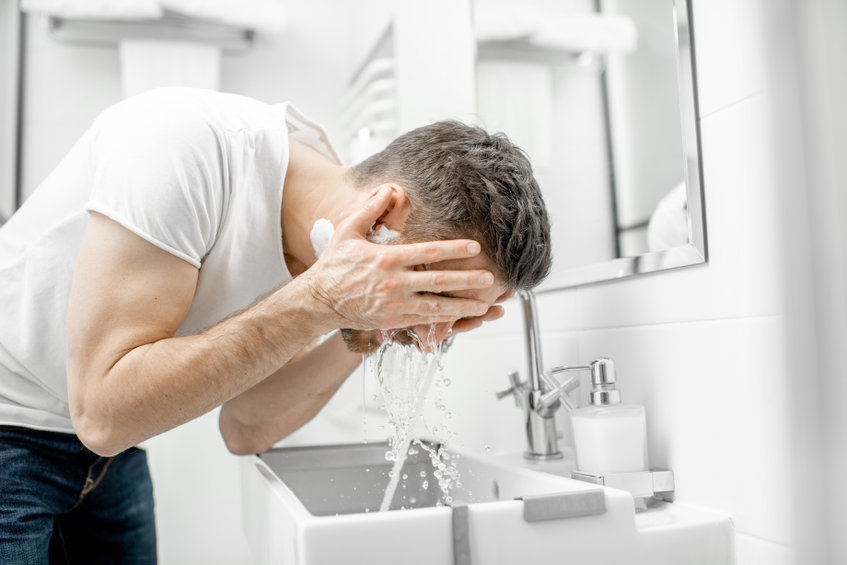 A man demonstrates his men's skincare routine as he splashes water onto his face over a white sink
