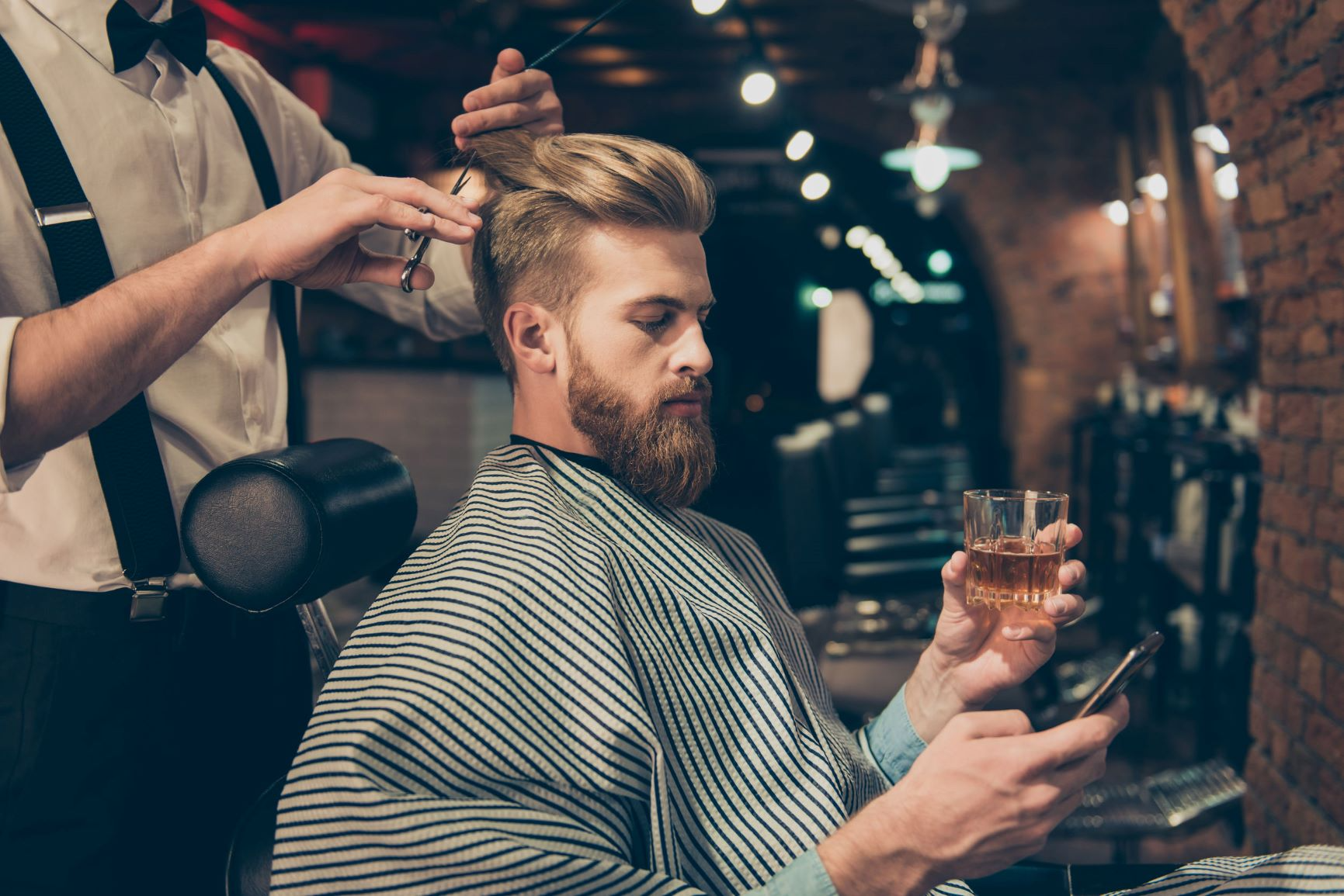 Man receiving undercut haircut from barber, holding glass and cellphone