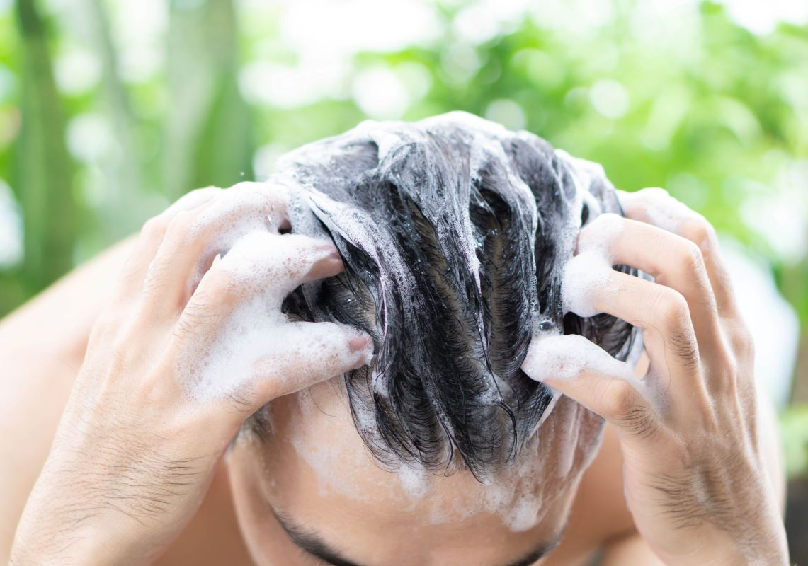Man applying moisturizer in front of mirror