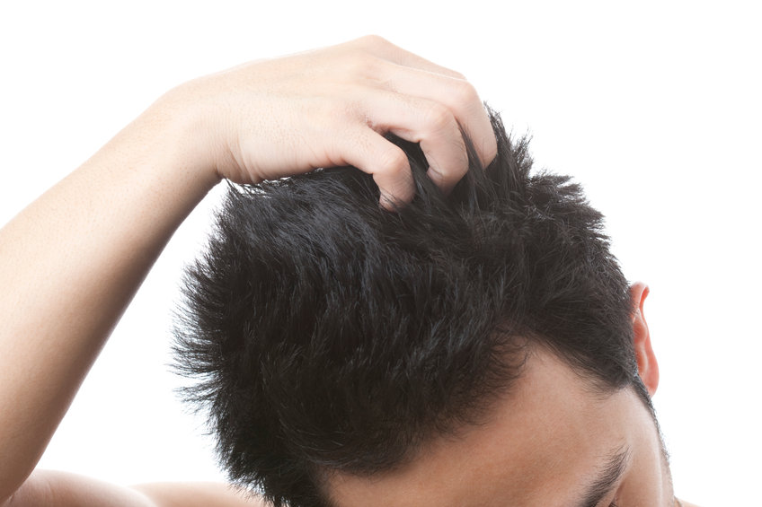A man moves his fingers through his dry hair