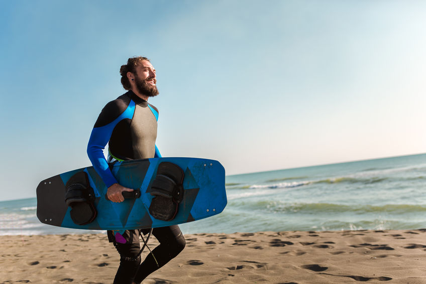 Bearded man runs on the beach while carrying a surfboard