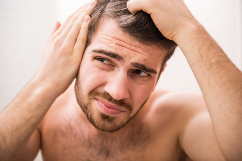 A man inspects his receding hairline and considers how to prevent hair loss