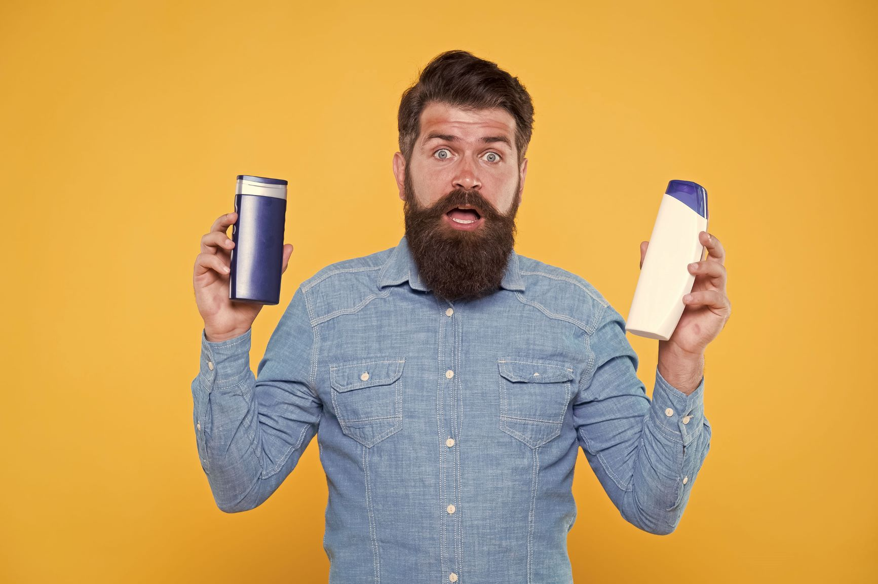 Bearded man holding hair care products in his hands