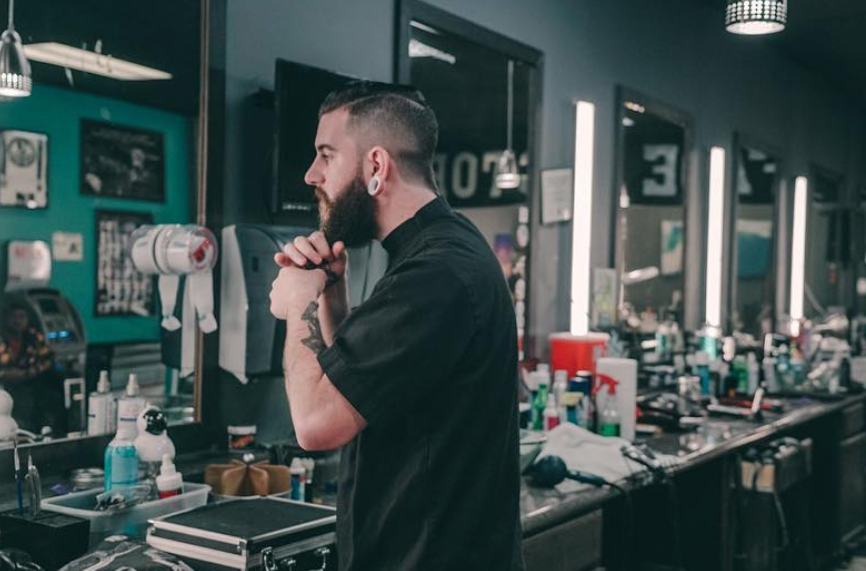 Man using the palms of his hands to rub some Johnny Slicks Oil Based Pomade into his long beard.