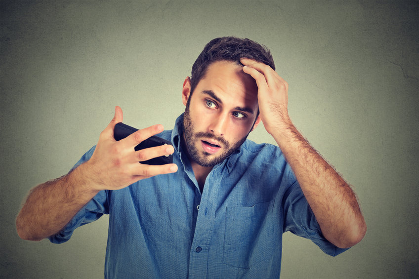 Shocked young man looks at himself in a phone camera to observe his receding hairline