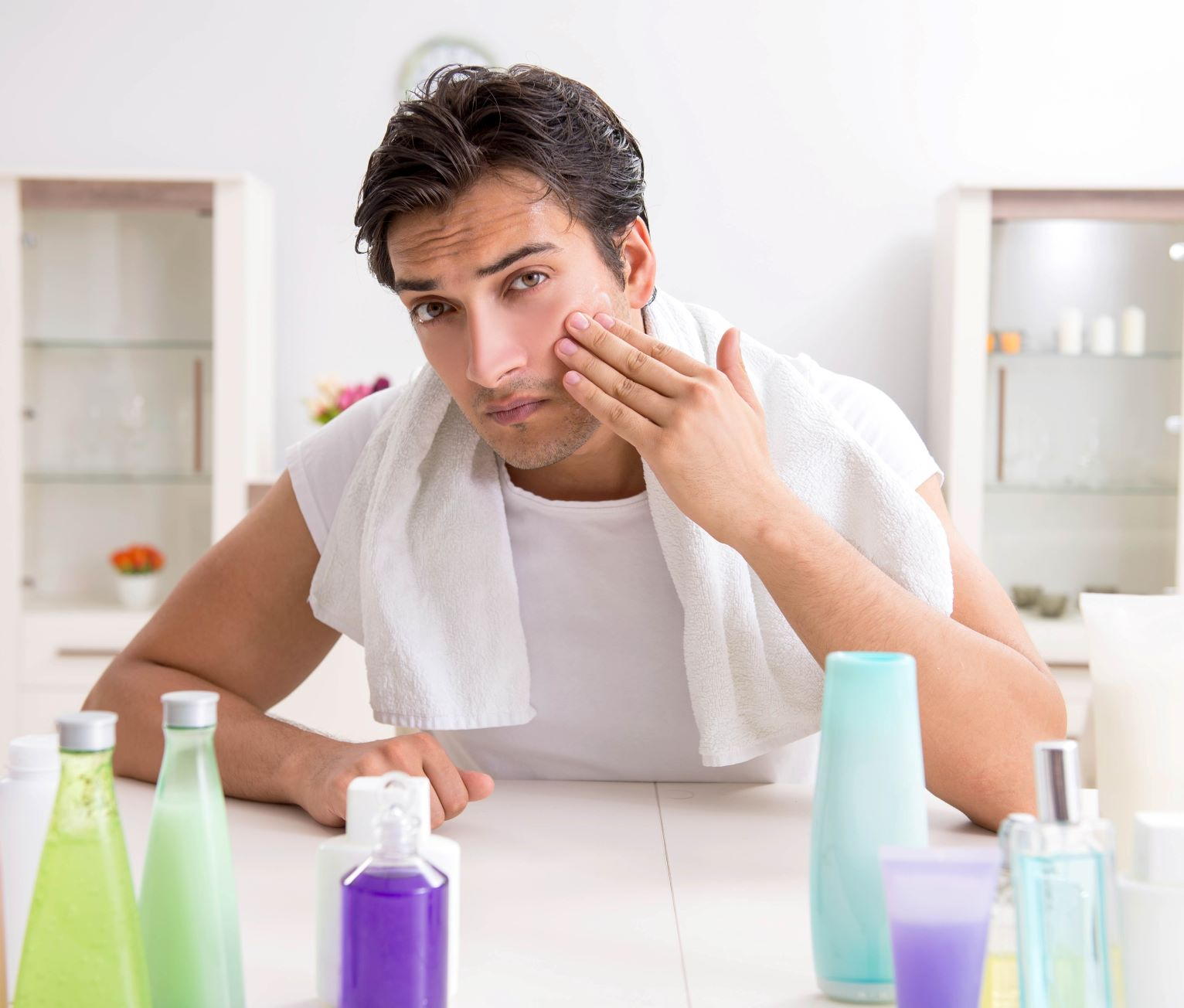Man applying moisturizer to his face as part of his self-care routine