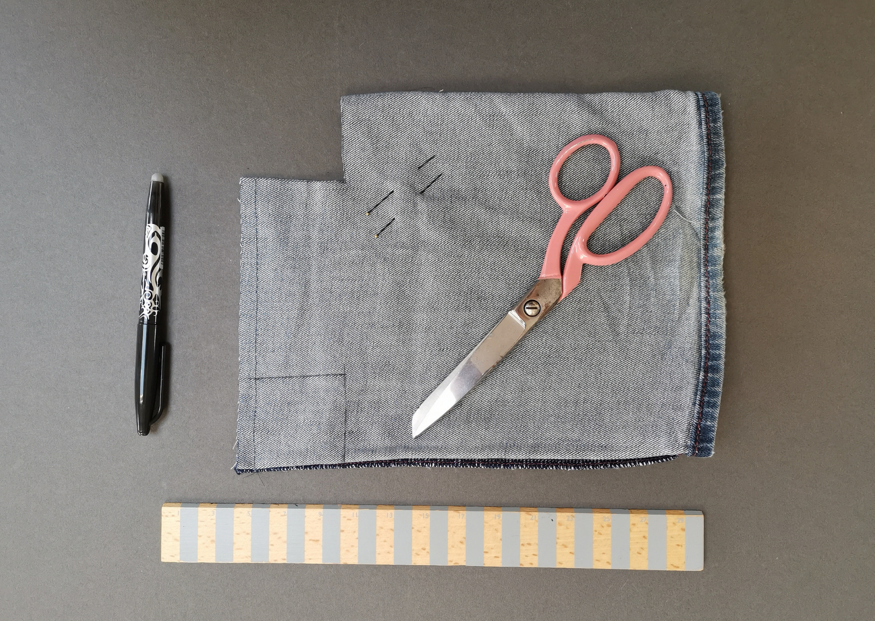 Leg of a pair of jens cut off at teh ankel with a pair of pink scissors, two pins, a pen and a ruler.  A square has been cut at the bottom to show the first stage of making a boxed bag.