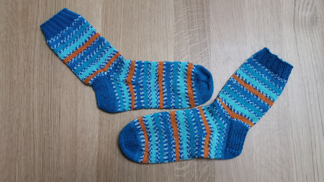 Wooden floor with blue, white and orange striped socks lying flat.