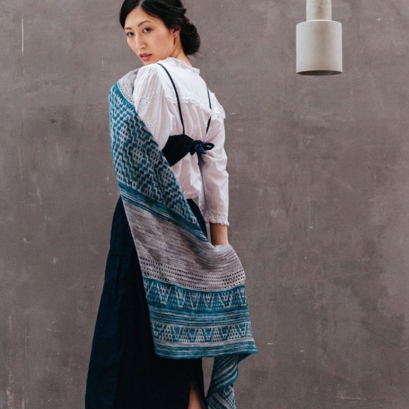 Model shows of Anna's Clean Lines Shawl.  The shawl has solid sections in mid-grey and mosaic sections in the same grey and a bright/dark teal.  The mosaic uses triangular motifs.