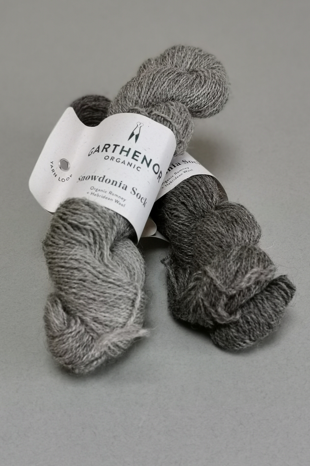 grey background with two skeins of a lustrous grey wool.  One is silver grey and the other is steel grey.
