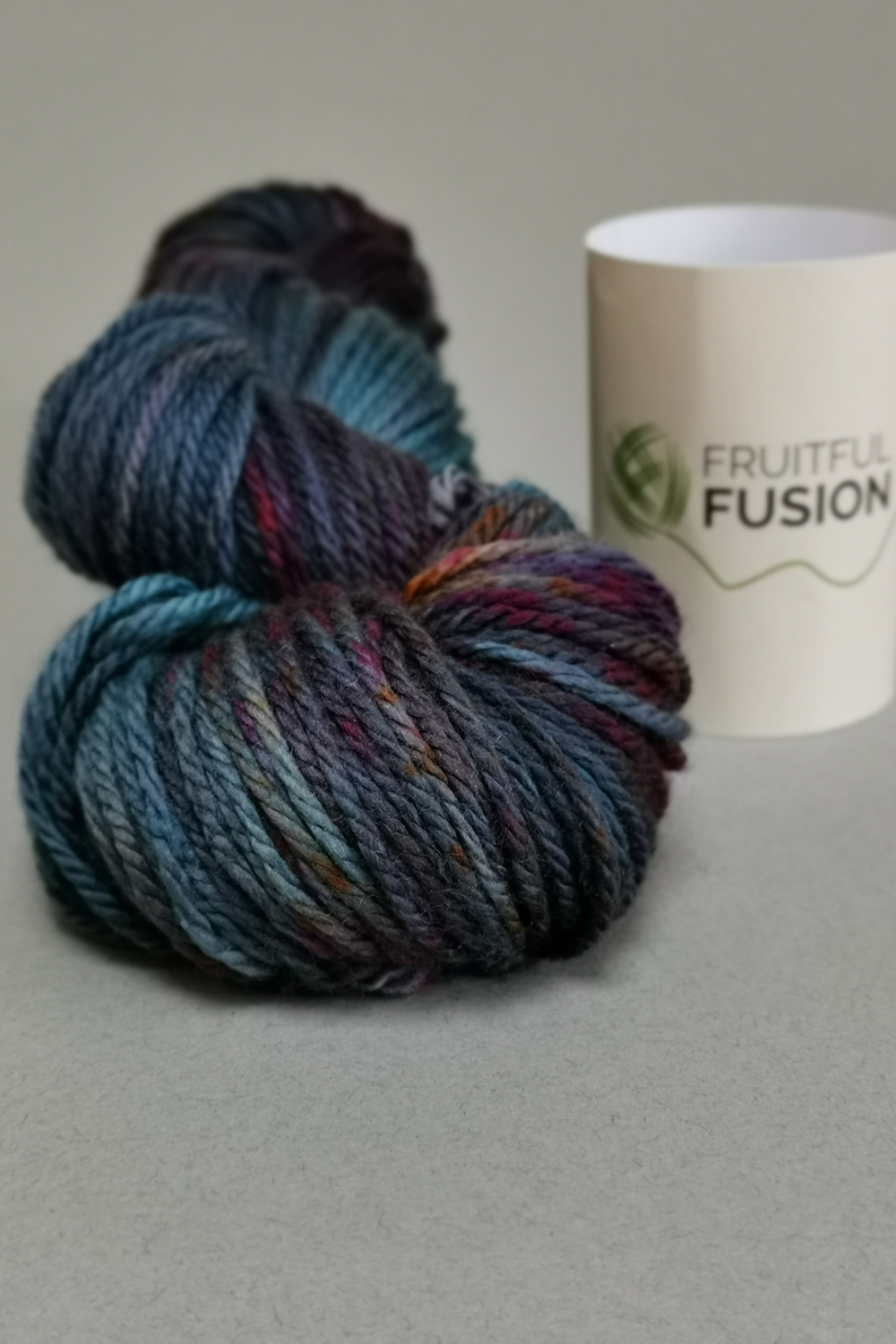 grey background with a skein of plum yarn from Fruitful Fusion.  Mid bluey purple with flashes of burnt orange, marroon and brown speckles.
