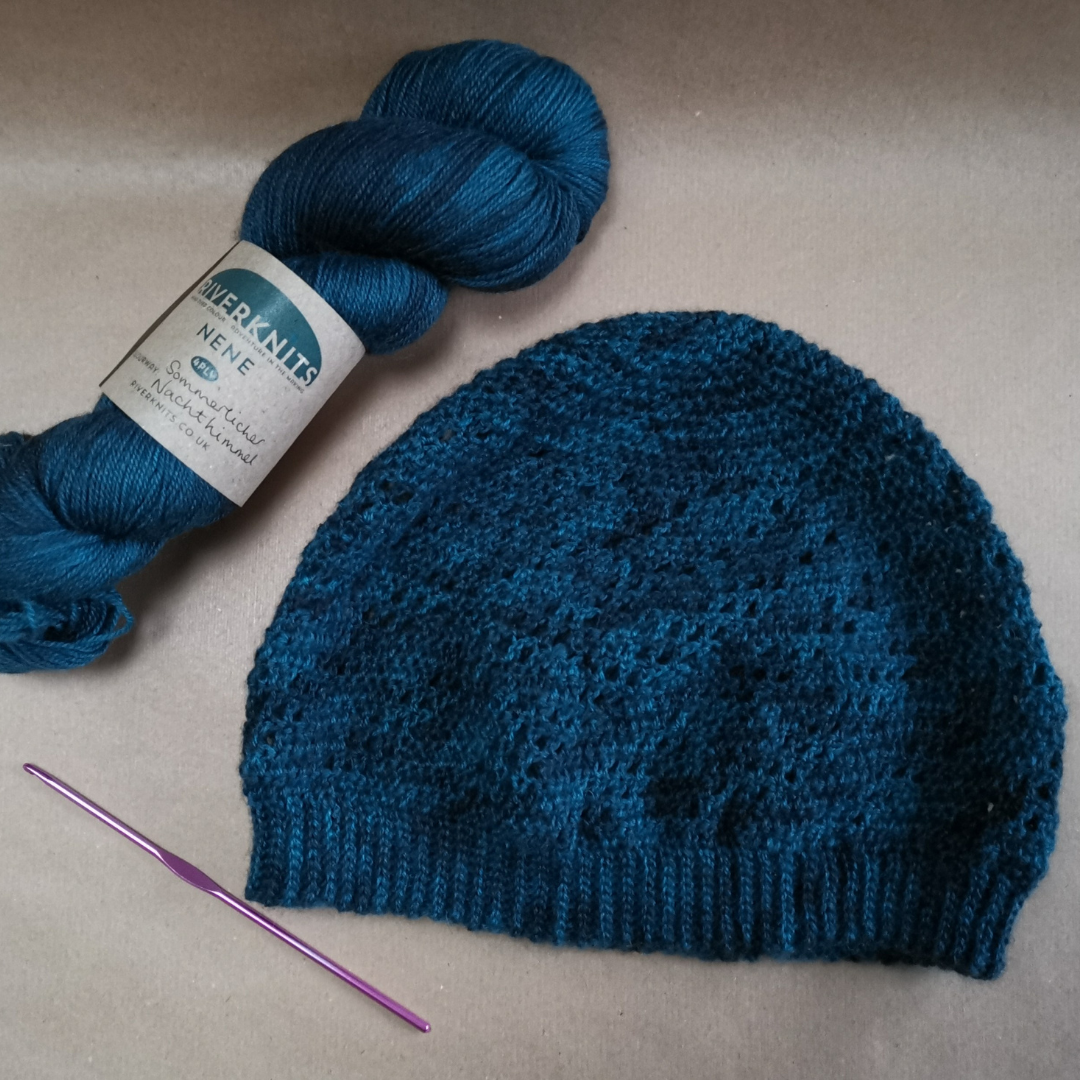 Finished hat on brown paper.  A crochet hook lies to the left and a skein of dark teal vareigated yarn above it from RiverKnits.  The hat has a spiral lace pattern that lows around it.