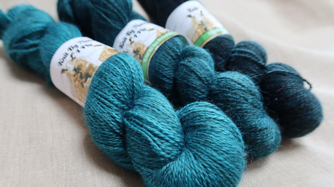 John Arbon Textiles Knit by Numbers wool in thre shades of teal, mod to dark on a beige inen background