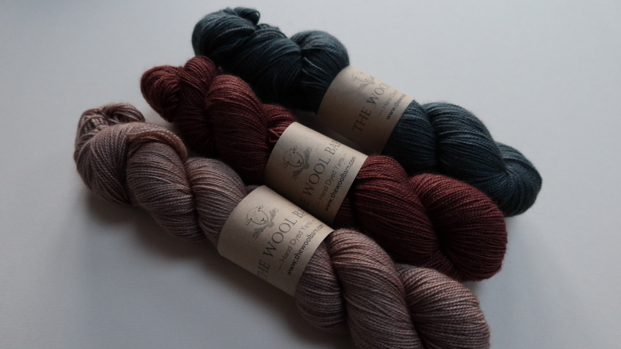 Three skeins of yarn lying diaginally.  They have a high twist and soli dcoloours.  Peachy, almond brown, warm redish brown and dark, slate blue.