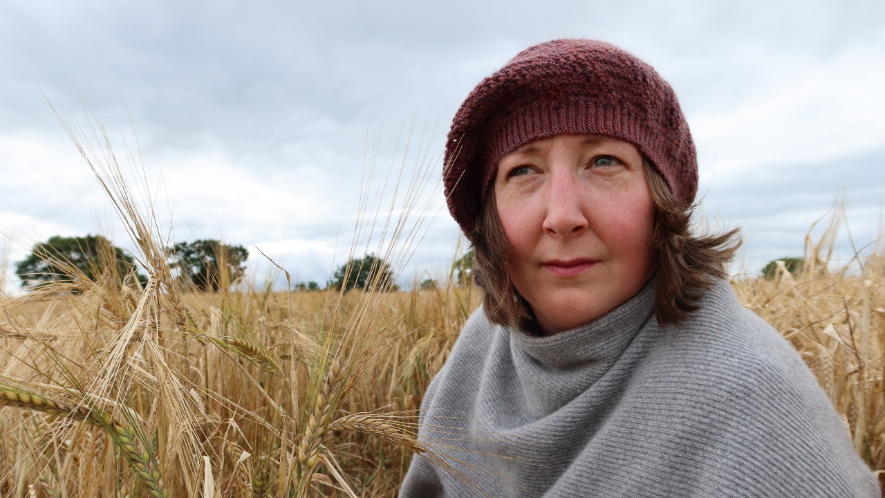 Headshot of me with short brown hair in a cornfield wearing a dark rose pink Tam hat which is one of the styles from the Positivity Spiral Hat pattern..