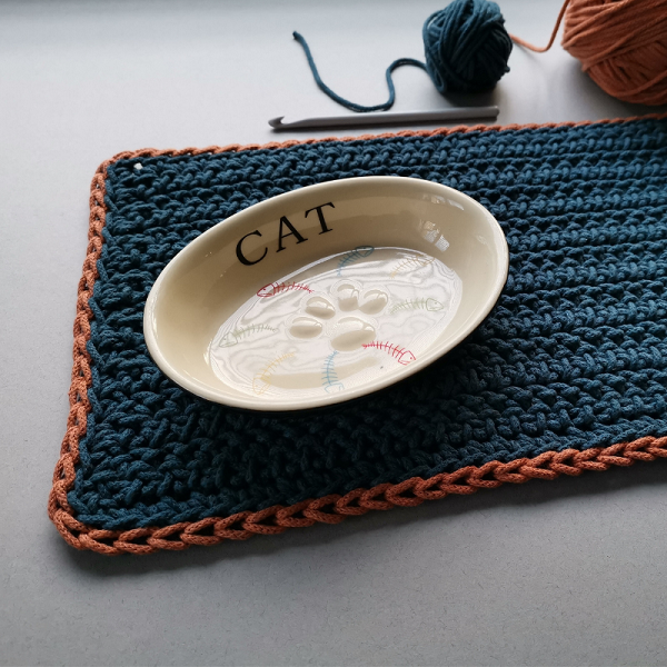 Peacock blue cotten cata food mat with a teracotta coloured trim.  Cat bowl on top and left over yarn showing.