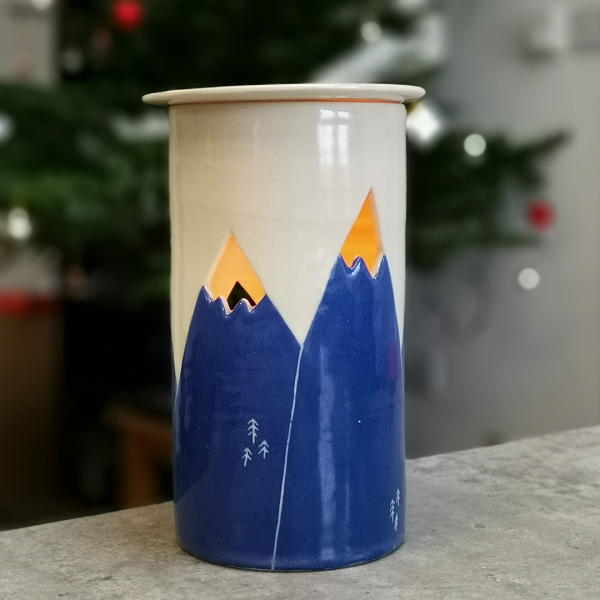 A ceramic oil burner with blue mountains and cut out mountain peaks for the glow to show through.