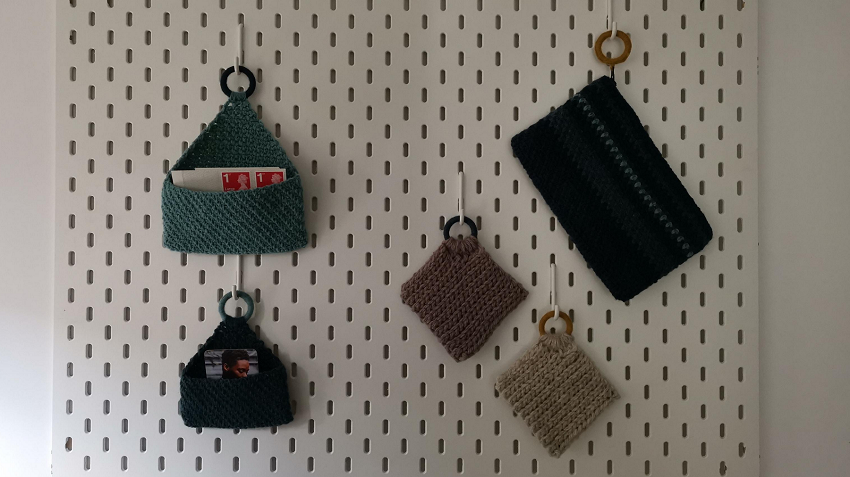 Wall storage panel has crocheted storage hanging from it.  One for stamps, one for business cards, a purse and two coasters.
