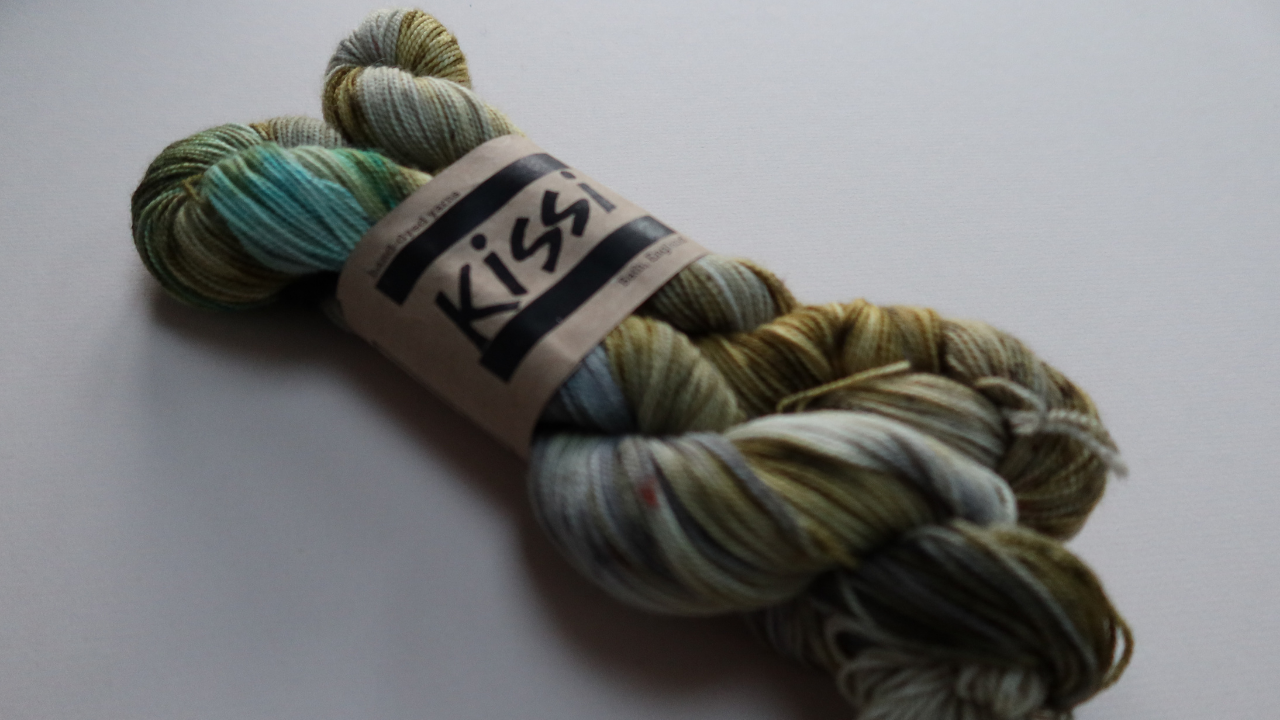 """Two 50g skeins of a high twist yarn held together with a ball band with """"Kissi"""" on it.  The skeins are in greens, mid turquoise with patches of grey."""