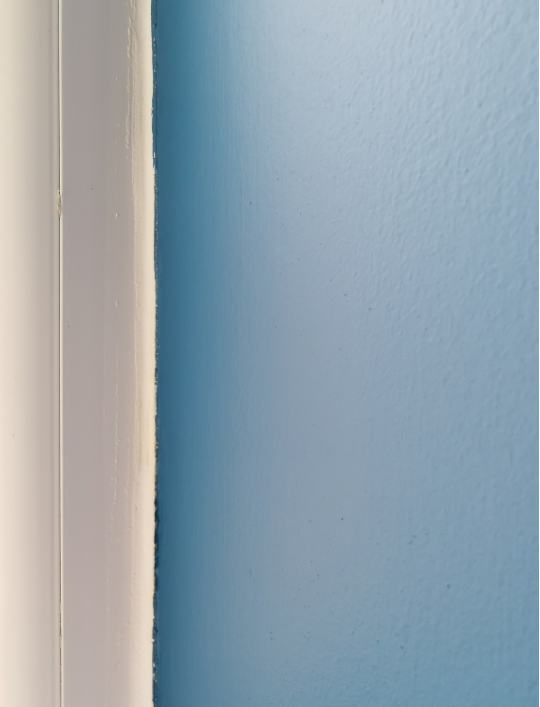 The edge of a UPVC window frame with a neat drak blue paint edge rightup to the frame.