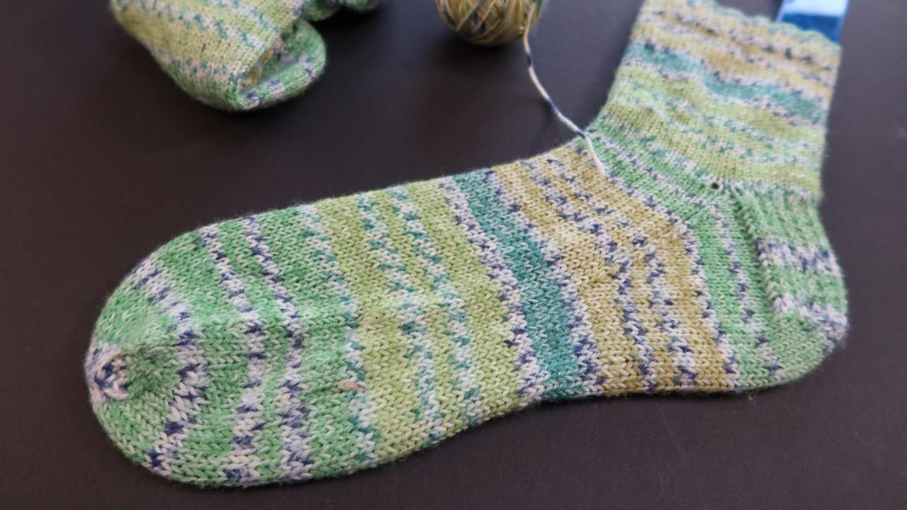 A green striped sock on a blue sock blocker.  Three shades of green striped with a white/blue faux Fair Isle band inbetween.
