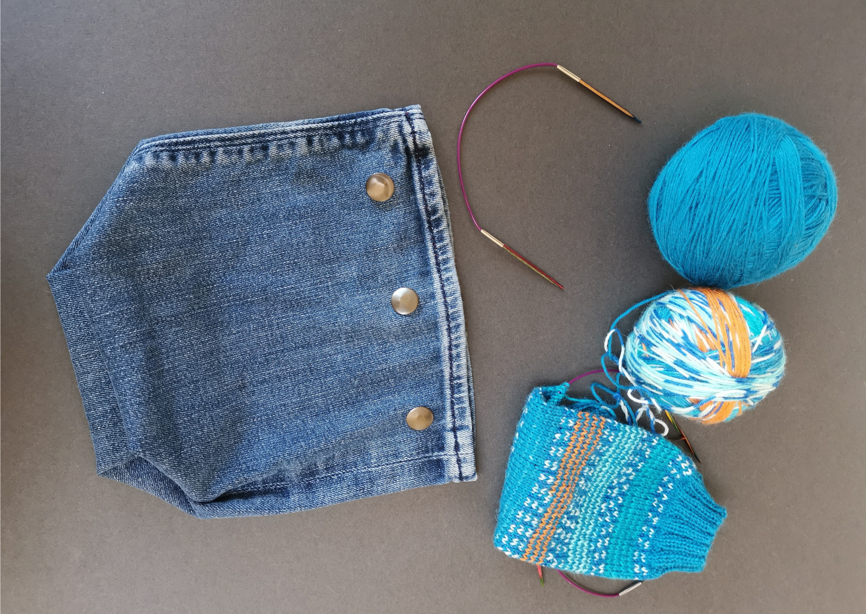 The same idea for the plant pot but with metal poppers added to make it into a project bag for sock knitting.  Turquoise and orange yarns, a small knitting needles and a partially made sock are to the right.